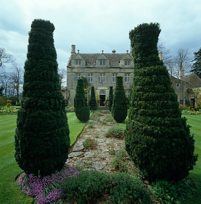A stone path llined with clipped yew trees leads to the door of this English country house