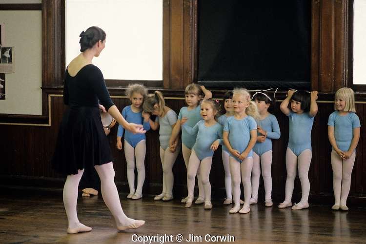 Young ballet dancers at a ballet class standing against the wall listening to the instructions from the ballet teacher.