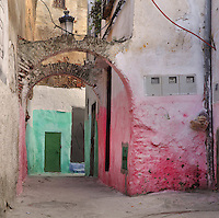 A narrow street with archways and pink and green painted walls, in the medina or old town of Tetouan on the slopes of Jbel Dersa in the Rif Mountains of Northern Morocco. Tetouan was of particular importance in the Islamic period from the 8th century, when it served as the main point of contact between Morocco and Andalusia. After the Reconquest, the town was rebuilt by Andalusian refugees who had been expelled by the Spanish. The medina of Tetouan dates to the 16th century and was declared a UNESCO World Heritage Site in 1997. Picture by Manuel Cohen