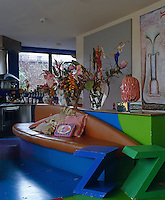 A bespoke leather sofa built into a wooden unit is accompanied by a pair of coloured stools in the shape of a 'Z' in the open-plan living room