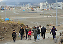 March 11, 2012, Rikuzentakata, Japan - A Japanese family makes its way to the family grave at Rikuzentakata, Iwate Prefecture, some 402 km northeast of Tokyo, on Sunday, March 11, 2012..Memorial ceremonies were held throughout Japan to mark the one year anniversary of the massive earthquake and tsunami that struck the country?fs northeastern region, killing just over 19,000 people and unleashing the world?fs worst nuclear crisis in a quarter century. The quake was the strongest recorded in the nation?fs history, and set off a tsunami that towered more than 65 feet in some spots along the northeastern coast, destroying thousands of homes and wreaking widespread destruction. (Photo by Natsuki Sakai/AFLO) AYF -mis-