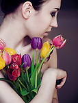 Young girl's profile, wish dark hair and make up and pale skin, holding a bunch of colourful tulips with simple background.