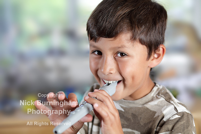 A young boy plays a recorder with concentration - shallow depth of field with copy space to left