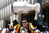 Ben Lovejoy #12 of the Pittsburgh Penguins hoists the Stanley Cup on stage during the victory parade in downtown Pittsburgh, Pennsylvania on June 15, 2016. (Photo by Jared Wickerham / DKPS)