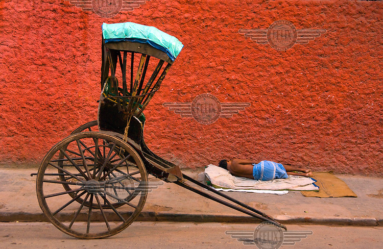A rickshaw puller takes a rest on the pavement by his cart. Despite numerous atempts to ban them Kolkutta remains the only place in India where hand drawn rickshaws are still found.