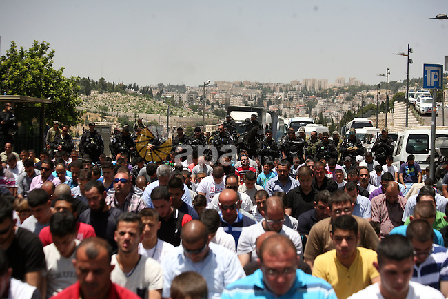 Palestinian Muslim worshipers attend the Friday prayers in the East Jerusalem neighbourhood of Ras al-Amud after being refused entry into the Al-Aqsa compound in Jerusalem, 30 May 2014. The Israeli police restricted the entrance to the Al-Aqsa mosque and permitted only men over the age of 45 due to intelligence reports of planned disturbances by Palestinians on al-Aqsa compound. Photo by Saeed Qaq