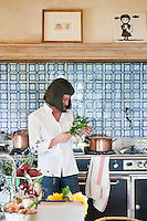 Portrait of chef Maddalena Caruso cooking in her country kitchen with fresh produce from her vegetable garden