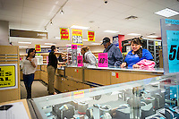 Customers search for bargain jewelry at the soon to be closing Sears store in the New York borough of the Bronx on Sunday, October 26, 2014. Sears Holdings announced that it will close 77 Sears and Kmart stores prior to the Christmas holiday. This is in addition to previously announced closings and over 7000 jobs will be lost. (© Richard B. Levine)