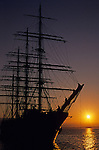 Sunset over Puget Sound and the Olympic Mountains with tall ship silhouetted along the Seattle waterfront Seattle Washington State USA