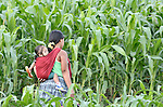 A woman walks home through a corn field after washing herr laundry in a river in Las Flores, Ixcan, Guatemala.