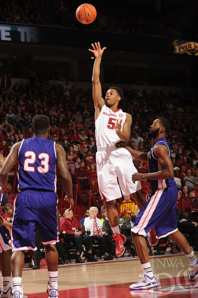 NWA Media/ANDY SHUPE - Arkansas' Anthlon Bell (5) takes a shot over Northwestern State's Marvin Frazier, right, and Zeek Woodley (23) during the second half of the Razorbacks' 100-92 win Sunday, Dec. 28, 2014, in Bud Walton Arena in Fayetteville.