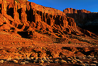 731350032 sunrise lights up the red sandstone formations near the fluted wall on the western side of capitol reef national park in utah