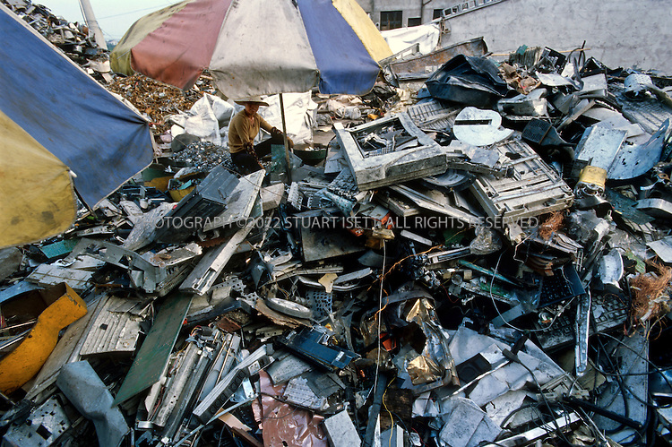 7/2/2005--Taizhou, Zheijiang Province, China..Piles of illegal e-waste sit outside homes in the village of Quingyu where it will be broken down and processed, releasing toxic waste into the local environment...The eastern Chinese port city of Taizhou has now become the center for much of the illegal trade in e-waste (computer waste). 24 hours a day ships arrive in the city?s harbor carrying cargo of waste, including millions of computer parts. These parts flow out of the port in trucks into the city and hinterland where hundreds of tiny work shops break down the parts, melting off the precious metals and using acids to separate gold from circuits boards, mobile phones, monitors and other computer parts. Neighborhoods are filled with the noxious and toxic fumes of this unregulated industry and thousands of men, women and children are exposed to a toxic cocktail of fumes and dust released. . .Photograph By Stuart Isett.All photographs ©2005 Stuart Isett.All rights reserved.