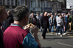 West Ham United 2 Crystal Palace 2, 02/04/2016. Boleyn Ground, Premier League. A man eating a snack on the corner of Green Street and Castle Street near the Boleyn Ground before West Ham United hosted Crystal Palace in a Barclays Premier League match. The Boleyn Ground at Upton Park was the club's home ground from 1904 until the end of the 2015-16 season when they moved into the Olympic Stadium, built for the 2012 London games, at nearby Stratford. The match ended in a 2-2 draw, watched by a near-capacity crowd of 34,857. Photo by Colin McPherson.