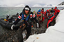 Norway, Svalbard, tourists climbing on shore after Zodiak drive