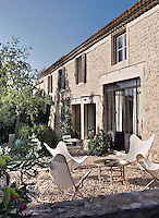 The farmhouse of an old vineyard in Provence has been sympathetically restored with additions, such as the metal french windows, designed in keeping with the traditional style