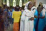 Women dance in the aisle as a children's choir sings during a worship service of Nuer refugees from South Sudan who live in Cairo, Egypt. The service took place at St Andrews United Church of Cairo.