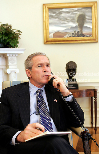 Working in the Oval Office of the White House in Washington, D.C., United States President George W. Bush talks with U.S. Secretary of State Colin Powell and Governor Jeb Bush of Florida during their trip to tsunami-affected areas Tuesday, January 4, 2005. .Mandatory Credit: Eric Draper / White House via CNP