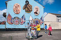 Belfast, Northern Ireland, United Kingdom, May 2011. Children play in front of a mural. Colourful murals with militaristic images are the silent reminders of the sectarian violence. During The Troubles, the Greater Shankill and its residents were subjected to bombings and shootings by Irish republican paramilitary forces, the most notable of which was the Shankill Road bombing. The Shankill was also a centre for loyalist paramilitarism. The modern Ulster Volunteer Force (UVF) had its genesis on the Shankill. Similarly the Ulster Defence Association, established in September 1971, also began on the Shankill. For decades travellers stayed away from the sectarian violence, but since the end of'The Troubles' more and more people start discoving the beauty of Belfast and the Antrim Coast Causeway. Photo by Frits Meyst/Adventure4ever.com