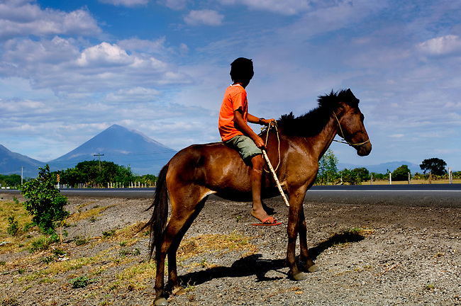 Boy on a horse waits to cross a main highway in northwestern Nicaragua.  The San Cristobal Volcano can be seen in the background.