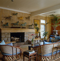 A collection of bronze weathervanes in the shape of horses at full gallop is displayed above the fireplace in this light living room