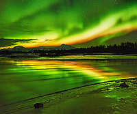 A high-energy aurora sends brilliant streamers of green, yellow and red over Mount Foraker, Mount Hunter and Mount McKinley and is reflected in the Talkeenta River outside Talkeetna, Alaska, on an early winter night.