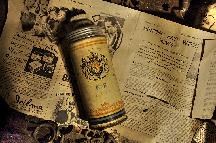 An old thermos flask lying on an old piece of newsprint in a box of nuts and bolts