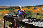 Local woman braai-ing meat and wors in flowers in Namaqua National Park, Namaqualand, Northern, Cape, South, Africa
