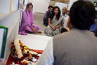Staff and guests sit on the floor barefooted in respect of the puja (prayer and blessing) at the opening ceremony of the new Bill &amp; Melinda Gates Foundation office in New Delhi, India on 17th December 2010. Photo by Suzanne Lee for Gates Foundation