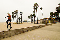 A unicyclist rides on a wall along the Santa Monica Boardwalk on Thursday, Aug 23, 2012.