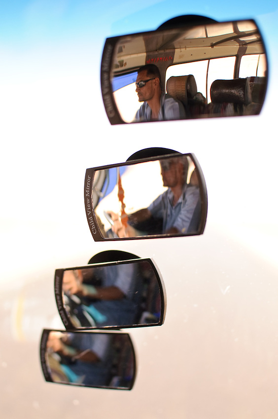 An Egyptian minibus driver in his rear view mirrors, in Dakhla Oasis