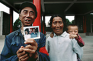 September, 1985. Shaanxi Province, China. New generation villagers showing photos of their family members who participated with Mao Zedong in the Long March.