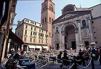 Mantova, centro storico, basilica di Sant'Andrea. Gente seduta ai tavolini di un bar.<br /> Mantua, old town centre, Sant'Andrea basilica. People sitting at an outdoor cafe.