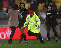 A security guard lines up a tackle on a pitch invader as Ma'a Nonu looks on during the International Test Match between the NZ All Blacks and France at Westpac Stadium, Wellington, New Zealand on Saturday 20 June 2009. Photo: Dave Lintott / lintottphoto.co.nz