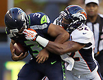 Seattle Seahawks quarterback Russell Wilson is face masked by Denver Broncos Wesley Woodyard at CenturyLink Field in Seattle, Washington on  August 17, 2013. The Seattle Seahawks beat the Broncos 40-10.     ©2013. Jim Bryant Photo. All Rights Reserved.