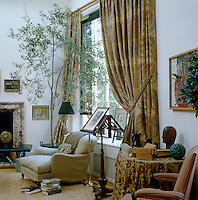 A large window in the living room is shielded by a series of individual cane roller blinds and framed by a generous curtain