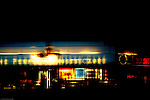 The transit area at London Heathrow airport with The Perfectionsts Cafe, restaurants and illuminated shops.