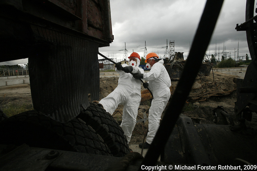Workers at the Chernobyl plant dig up and remove a radioactive crane that had been buried just west of the fourth-block shelter. In the months after the 1986 accident, vehicles used by liquidators often became too radioactive to continue using and were typically buried in unmarked sites.<br /> ------------------- <br /> This photograph is part the book of Would You Stay?, by Michael Forster Rothbart, published by TED Books in 2013. The photos come from Forster Rothbart&rsquo;s two long-term documentary photography projects, After Chernobyl and After Fukushima.<br /> &copy; Michael Forster Rothbart 2007-2013.<br /> www.afterchernobyl.com<br /> www.mfrphoto.com &bull; 607-267-4893 &bull; 607-436-2856<br /> 34 Spruce St, Oneonta, NY 13820<br /> 86 Three Mile Pond Rd, Vassalboro, ME 04989<br /> info@mfrphoto.com<br /> Photo by: Michael Forster Rothbart<br /> Date:  7/2009    File#:  Canon 5D digital camera frame 72172
