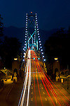 Cars cross the Lions Gate Bridge from Stanley Park in Vancouver, British Columbia to North Vancouver at night.