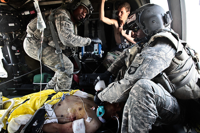 """Flight medic Staff Sgt. Rakheem Francis, 24, of Queens, N.Y., (right) and crew chief Sgt. 1st Class Lloyd Swaby, 36, of Fort Lauderdale, Fla. (left), with the 101st Combat Aviation Brigade's """"Shadow Dustoff,"""" treat an Afghan soldier who was severely wounded in a Taliban ambush near Kandahar, Afghanistan. The soldier died a short time later. Sept. 19, 2010. DREW BROWN/STARS AND STRIPES"""