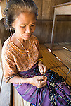 Woman ties thread for resist-dying. The thread will be used to weave traditional ikat.