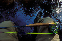 A fly rod rests on a fisherman's legs while sitting on the bank of a trout stream in Michigan's Upper Peninsula.