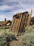 Leaning wooden outhouses behind the Methodist Church in the ghost town of Bodie, Calif.