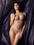 Young glamorous woman wearing beautiful beige lingerie standing surrounded by dark flowy fabric