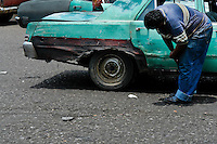 A Venezuelan driver checks his rusty American classic car from 1970s on the parking stand in Maracaibo, Venezuela, 10 May 2006.