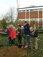 Grundschulklasse, Schulklasse hat im Schulgarten, Garten einen Baum gepflanzt