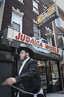 A Lubavitcher holds his prayer shawl, called a tallit katan, as he walks in the Crown Heights section of the the New York City borough of Brooklyn, NY, Monday August 1, 2011. Crown Heights hosts an important Chabad-Lubavitch community, one of the world's larger and best-known Hasidic movements in Orthodox Judaism.