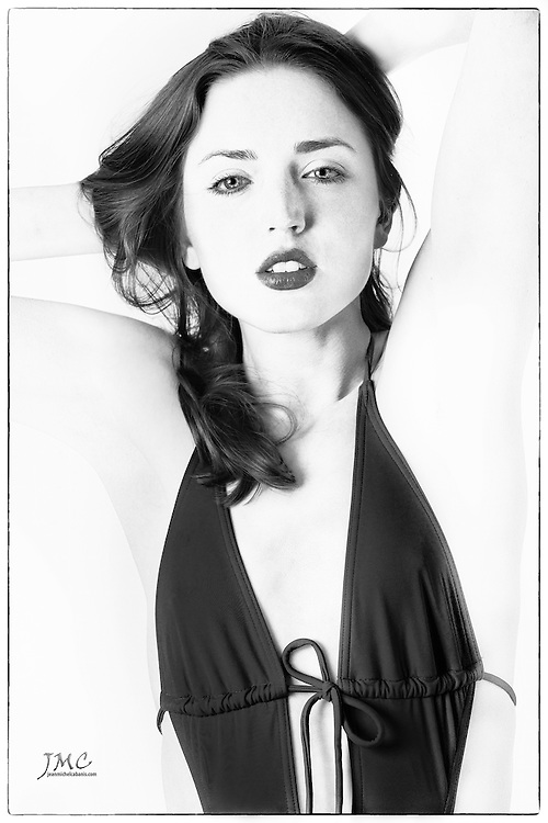 Black and white portrait of beautiful brunette fashion model in red swimsuit