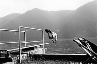 Switzerland. Canton Ticino. Castagnola. A man jumps in the lake from a diving board. He wears a swimmsuit and palms on both feet. Castagnola is distant 10 minutes from Lugano. © 1995 Didier Ruef