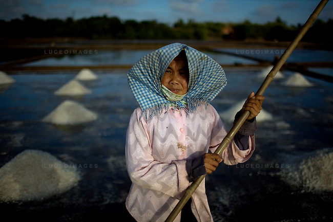 Salt people of Vietnam..Farmers harvest salt cultivated in rice-patty like fields in Ben Tre, a village in southern Vietnam. The salt season usually begins in January and ends in March as these are the driest months. Photo taken Friday, March 21, 2008. Kevin German / kevin@kevingerman.com